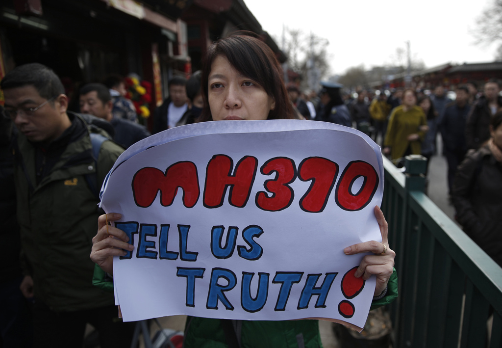 Catherine Gang, whose husband Li Zhi was onboard the missing Malaysia Airlines flight MH370, holds a banner as she walks outside Yonghegong Lama Temple after a gathering of family members of the missing passengers in Beijing