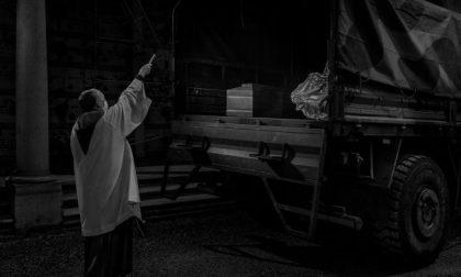 Un sacerdote novarese che benedice le bare di Bergamo tra le immagini simbolo del 2020